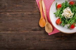 offset photo of salad on a placemat with wooden spoons on a rustic wooden table