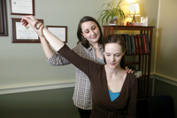 photo of a female doctor holding up the arm of a seated patient