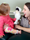 photo of female doctor entertaining baby with puppet