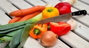 photo of carrots, leeks, peppers, onion, garlic and a chef knife