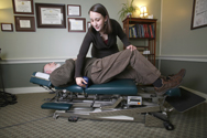 photo of a female doctor working with a male patient who is lying on his back