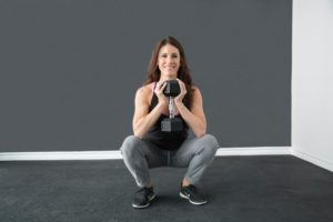 Smiling woman squatting with hand weights.